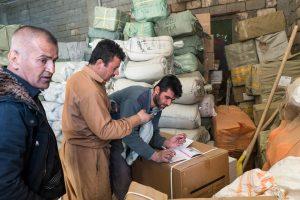 Village de Zale, Kurdistan, Irak, février 2017. Umit photographie un bon de transport pour le transmettre via l'application Telegram au marchand iranien qui a passé la commande.